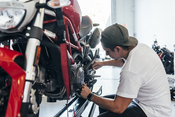 man repairing his motorcycle