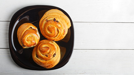 Raisin Buns in a black plate on white table