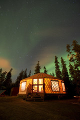 The Aurora Borealis (Northern Lights) over an illuminated yurt outside of Whitehorse in the Yukon Territory, Canada.