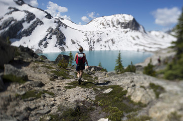 A young woman hiker walks towards a lake.