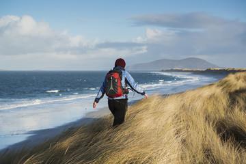 Woman walking through dune grass at beach