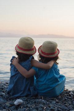 petites filles bras dessus bras dessous assises au bord de la mer