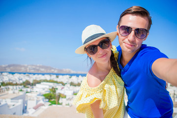 Selfie couple taking pictures at Mykonos island, Cyclades. Tourists people taking travel photos with smartphone on summer holidays.