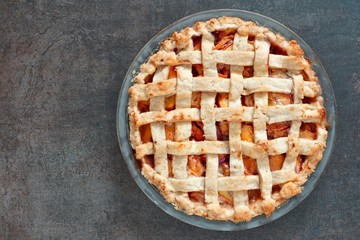 Rustic homemade peach pie in baking plate, above view on a stone background