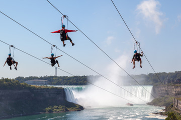 Wall Mural - Four unrecognizable people taking zipline ride at Niagara Falls Ontario Canada.  New zipline in Niagara Parks opened in the summer of 2016