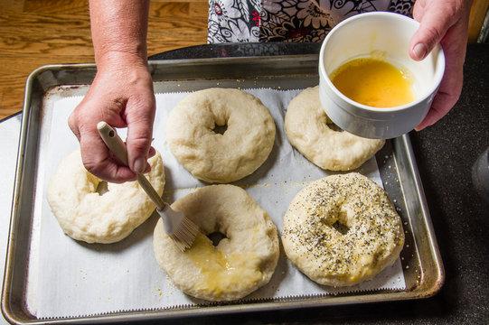Boiled bagels being seasoned for baking