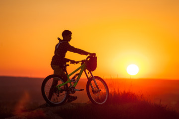 Silhouette of cyclist with mountain bike on the top of hill against evening sky with bright sun at the sunset