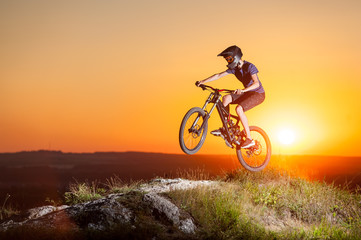 Cyclist jumping on a mountain bike on the precipice of hill against evening sky with bright sun. Cyclist is wearing sportswear helmet and glasses. Sunset