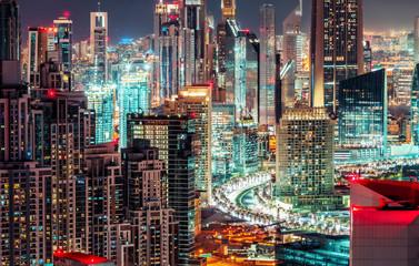 Multicolored nighttime skyline: big futuristic city with illuminated skyscrapers. Downtown Dubai, UAE. Scenic travel background.
