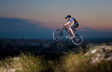 Extreme sport. Man in helmet and glasses flying on a mountain bike on the hill against evening sky and small town into the distance. Downhill cycling.