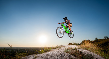 Young bicyclist in helmet and glasses making high jump on a mountain bike on the hill against blue sky. Bottom view