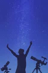 Girl enjoying starry skies with telescopes beside her.