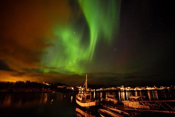 Aurora Borealis shine in sky over Ballstad, Lofoten, Norway