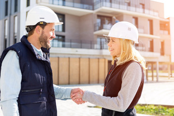 architect and worker handshaking on construction site