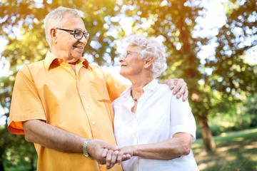 Happy senior couple hugging in park