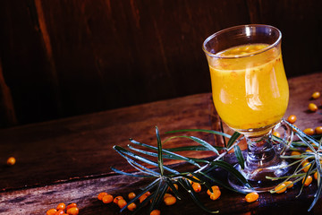 Sea buckthorn hot drink in a glass, fresh berries scattered on b