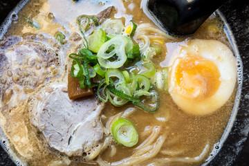 Tasty Japanese ramen soup bowl with pork, egg, and vegetables