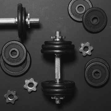 Dumbbells or weights on black table - Concept for workout - Flat
