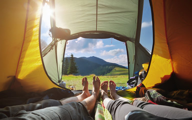 Two people lying in tent with a view of mountains. Carpathians.