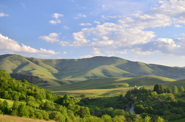 Poster Hill Landscape of Zlatibor Mountain. Green meadows and hills under blue sky with some clouds in springtime
