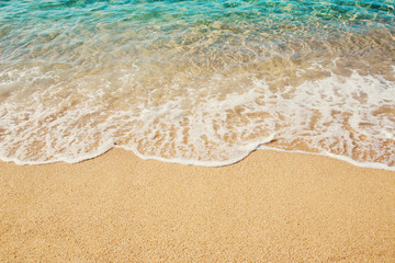 Background soft wave of Turquoise Sea with foam on sandy beach.