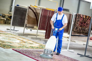 Worker cleaning with vacuum cleaner