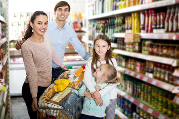 Family with two daughters shopping in local supermarket