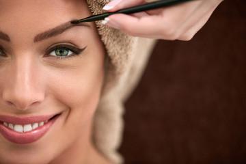 Smiling beautiful woman on professional make up treatment
