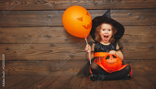 funny child girl in witch costume  for Halloween with pumpkin Ja