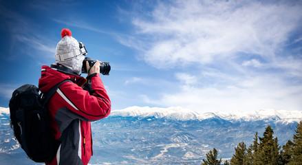 Female photographer take picture of winter landscape
