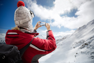 Woman on mountain making photo with smartphone