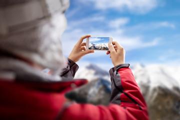 Woman take picture of winter landscape