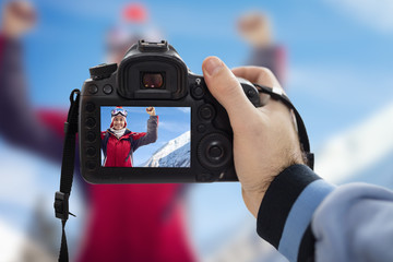 Photographer photographing happy woman on snowy winter day