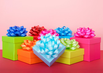rows of bright colorful party boxes with shiny bows on top, magenta table top, pink background. Copy space