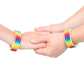 hands with a bracelet patterned as the rainbow flag. isolated on