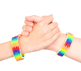 young girls shaking hands with a bracelet patterned as the rainb