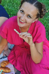 Retro-style girl in a vivid pink dress posing for a photo on a summer picnic