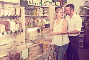 Couple selecting groats in store .