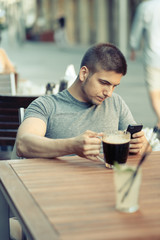 Man with mobile phone drinking beer