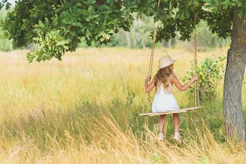 Pretty kid sitting on swing in meadow