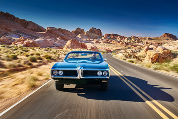 Wall Mural - guy driving cool vintage car through nevada desert