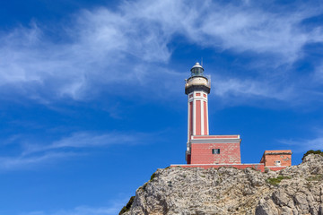 Lighthouse on a cliff in day time. Horizontal image with red and
