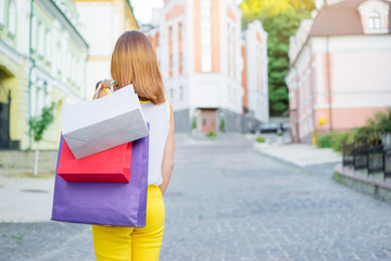 Shopping concept. Young woman holding paper bags outdoor. Back view.