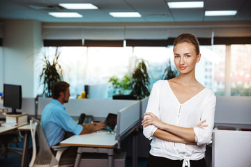 Young successful businesswoman smiling, posing with crossed arms, over office background.