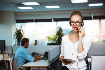Young beautiful female support phone operator speaking, consulting, over office background.