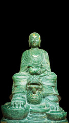 Old Buddha stone green Statue Isolated on a black Background.