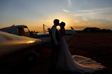 Silhouette of bride and groom near the airplane. Honeymoon concept