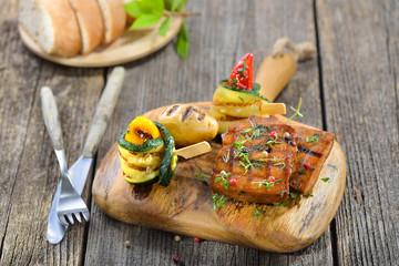 Vegan grillen: Grillteller mit Seitan dazu Zucchini-Röllchen, Grillkartoffel und Ciabatta serviert - Vegetarian grill platter with vegan seitan slices, courgette rolls and grilled potato