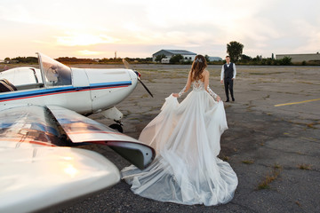 Beautiful bride in luxury wedding dress goes to meet the groom near the airplane