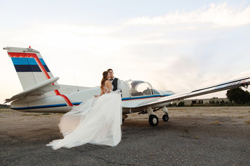 Bride and groom near the aircraft. Wedding travel concept